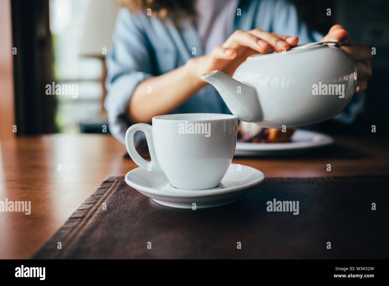Young woman pouring tea from teapot into cup sitting at table in restaurant, close-up. Scene of daily life female's hands making warming drink. - Stock Image