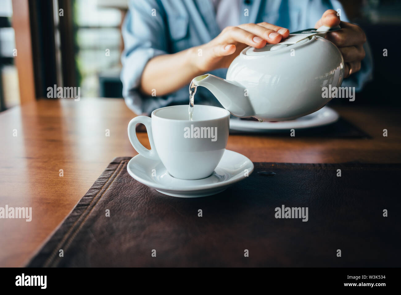 Female's hands pour tea from teapot into cup, close-up. Young woman prepares hot drink sitting at table in restaurant at daytime. - Stock Image