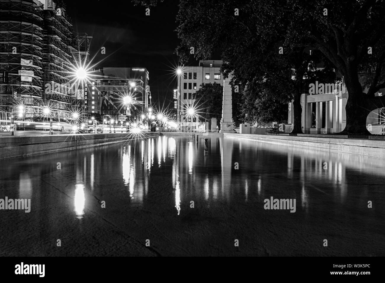 JFK Memorial Plaza Dealey Plaza in downtown Dallas at night. Water fountain. Triple Fountain at JFK Assassination Memorial Dallas, TX. Stock Photo