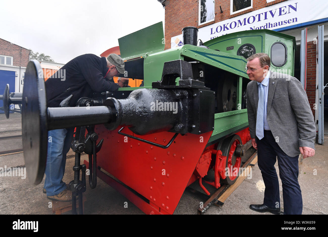 Nordhausen, Germany. 16th July, 2019. Bodo Ramelow (Die Linke, r), Prime Minister of Thuringia, visits the IFA Museum next to a 1922 shunting petrol locomotive. Ramelow's multi-day summer tour is entitled '#ZukunftThüringen - Kluge Köpfe, innovativen Prozesse' (#Future Thuringia - Clever minds, innovative processes). Credit: Martin Schutt/dpa-Zentralbild/dpa/Alamy Live News - Stock Image