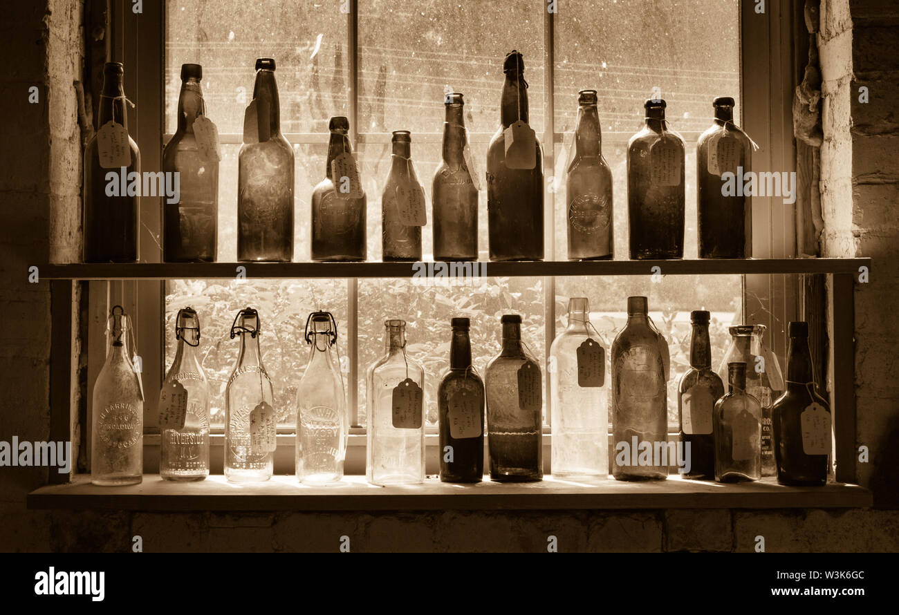 Sepia-toned image of shelves of antique glass bottles in a vintage store in the River Arts District, Asheville, North Carolina, USA. - Stock Image