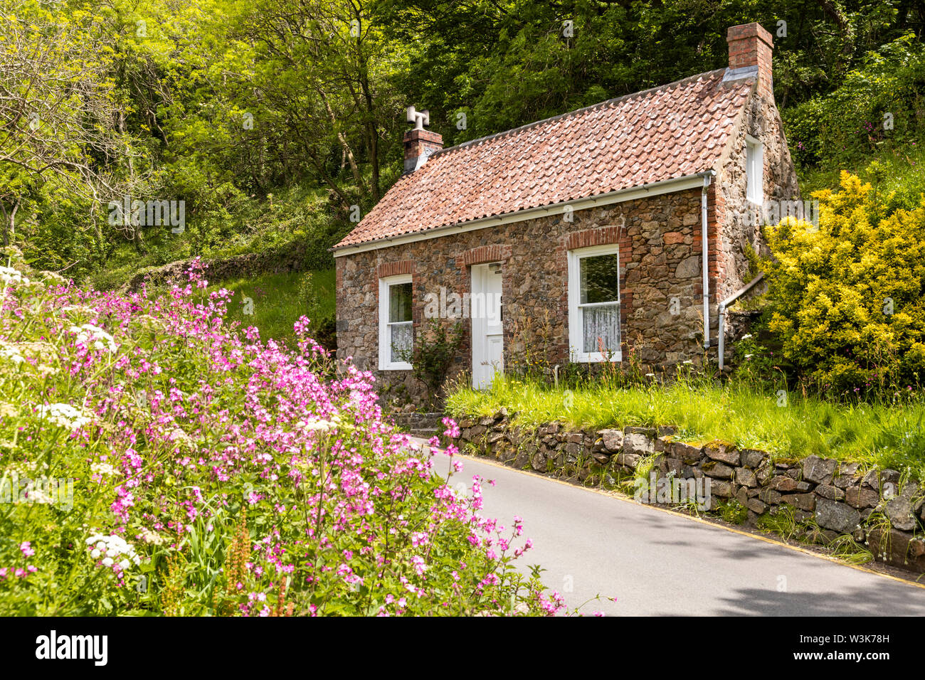 An old stone cottage beside the lane at Petit Bot, Guernsey, UK Stock Photo