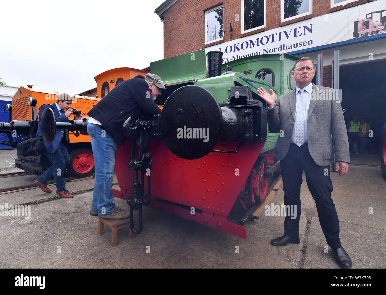 Nordhausen, Germany. 16th July, 2019. Bodo Ramelow (Die Linke), Prime Minister of Thuringia, visits the IFA Museum next to a 1922 petrol shunting locomotive. Ramelow's multi-day summer tour is entitled '#FutureThuringia - Clever minds, innovative processes'. Credit: Martin Schutt/dpa-Zentralbild/dpa/Alamy Live News - Stock Image
