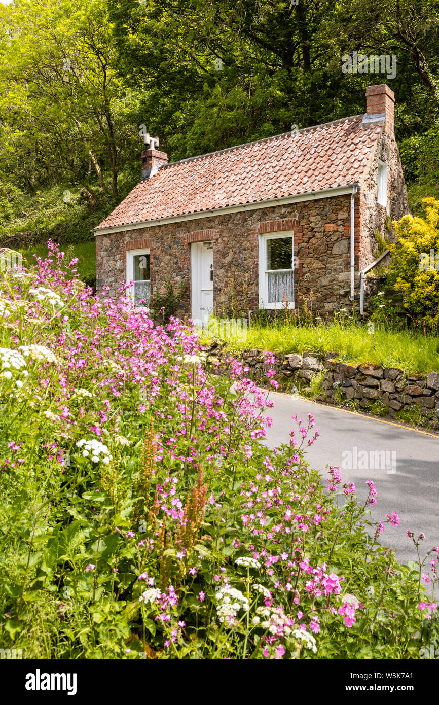 An old stone cottage beside the lane at Petit Bot, Guernsey, UK - Stock Image