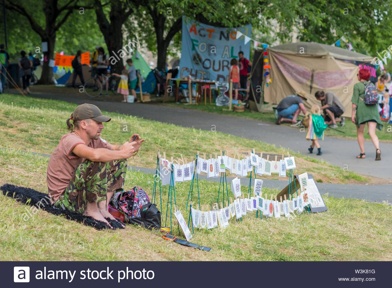 Bristol, United Kingdom - 16 July 2019: Extinction Rebellion member sells his wares in Castle Park as the group take over Bristol city centre for a second day as part of their Summer Uprising campaign drawing attention to environmental issues. Credit: Andy Parker/Alamy Live News - Stock Image