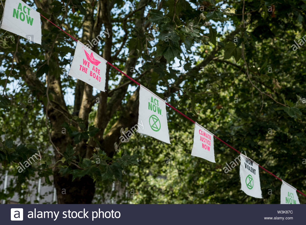 Bristol, United Kingdom - 16 July 2019: Extinction Rebellion banners and flags are strung up in the trees of Castle Park as protesters take over Bristol city centre for a second day as part of their Summer Uprising campaign drawing attention to environmental issues. Credit: Andy Parker/Alamy Live News - Stock Image