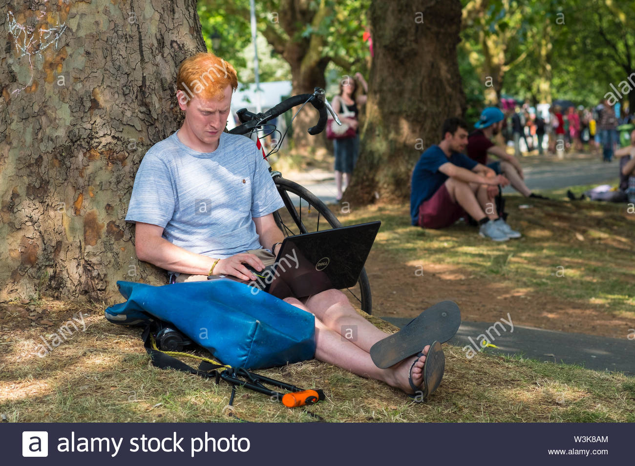 Bristol, United Kingdom - 16 July 2019: Extinction Rebellion protester takes a break in Castle Park as the group take over Bristol city centre for a second day as part of their Summer Uprising campaign drawing attention to environmental issues. Credit: Andy Parker/Alamy Live News - Stock Image