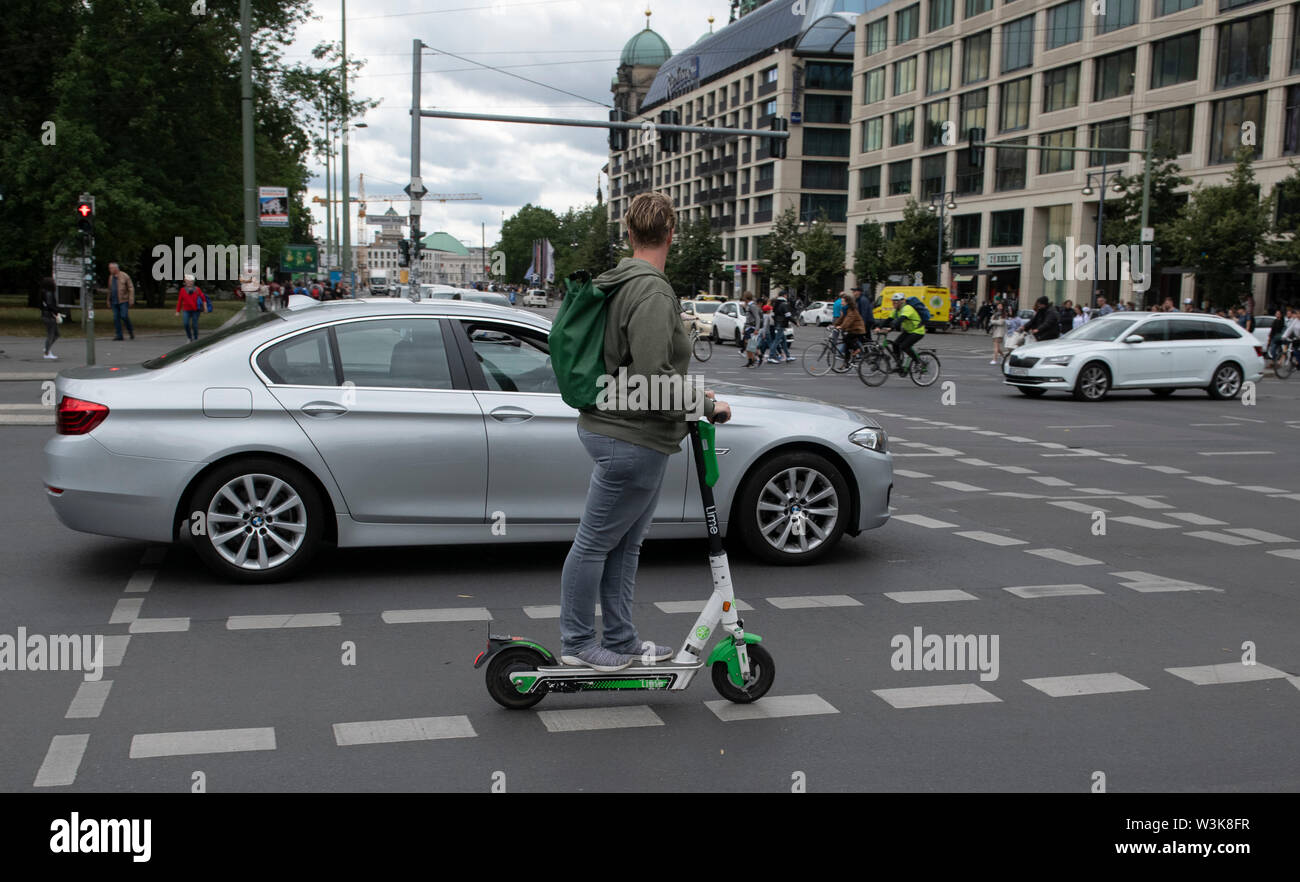 16 July 2019, Berlin: A man drives an electric scooter across a road.  Police have checked drivers of electric scooters near Berlin's Alexanderplatz. Photo: Paul Zinken/dpa - Stock Image