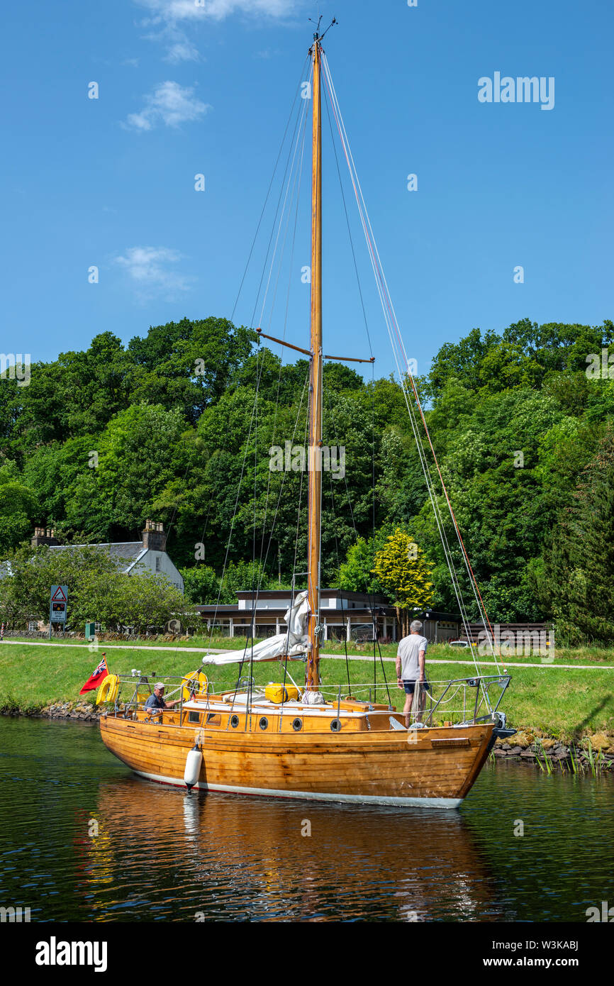 Wooden yacht exiting lock 5 and heading east towards Ardrishaig – Cairnbaan on Crinan Canal, Argyll and Bute, Scotland, UK Stock Photo