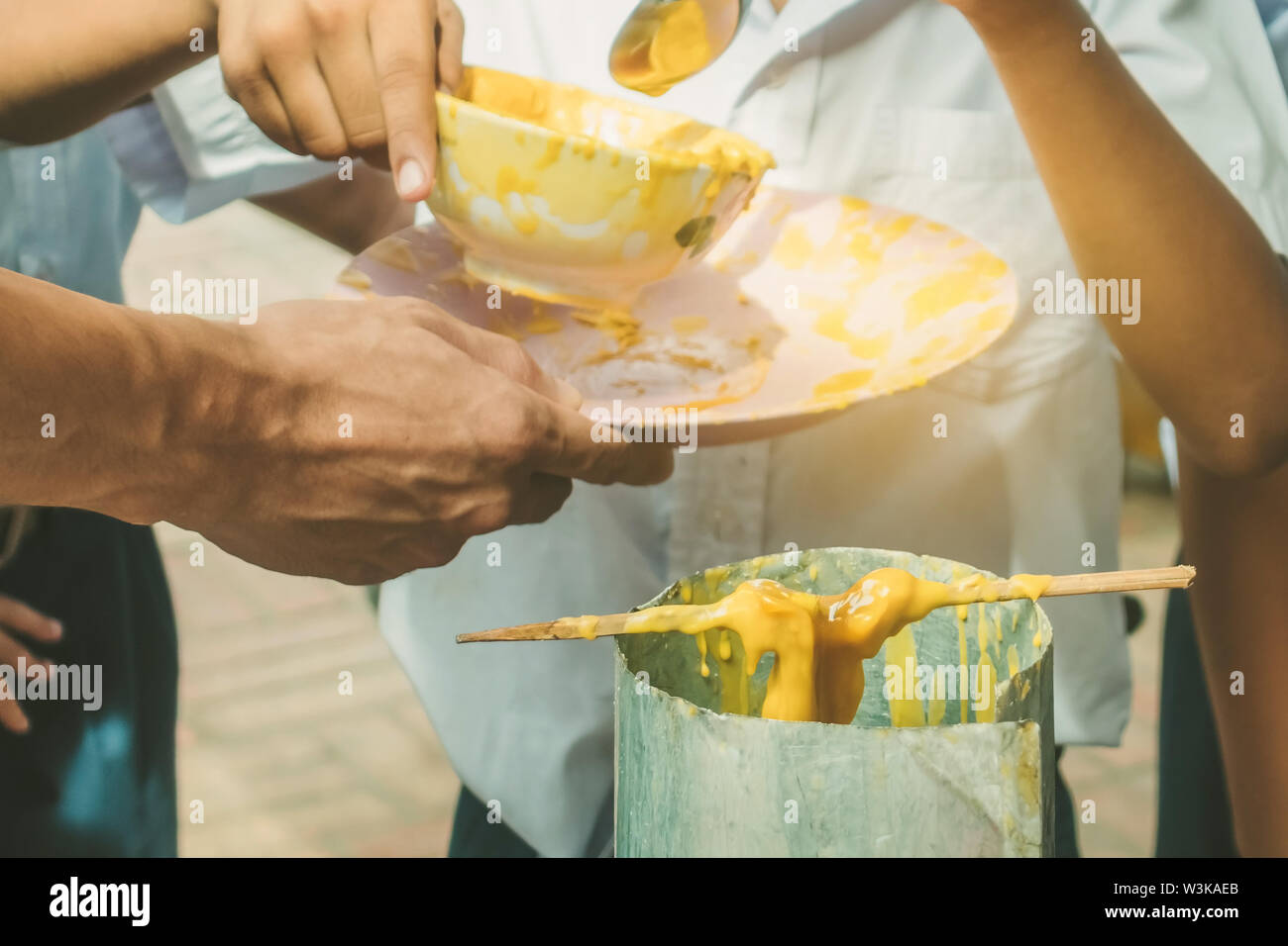 Students join melting cast candle offer to temple for Buddhist Lent Day, The tradition of the candle casting thai Buddhist. - Stock Image