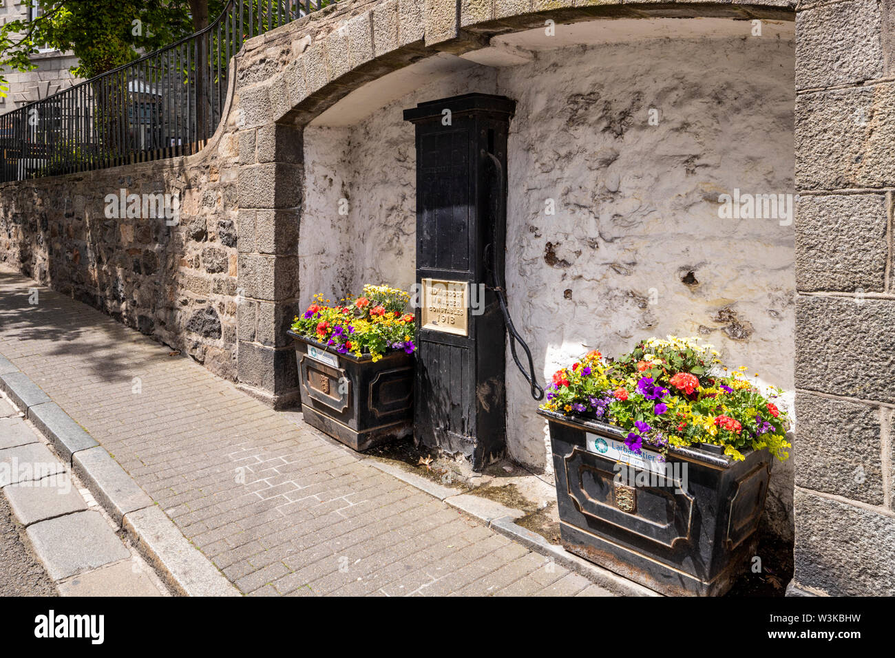 Floral displays beside an old public water pump dated 1918 in The Pollett under La Plaiderie, St Peter Port, Guernsey, Channel Islands UK Stock Photo
