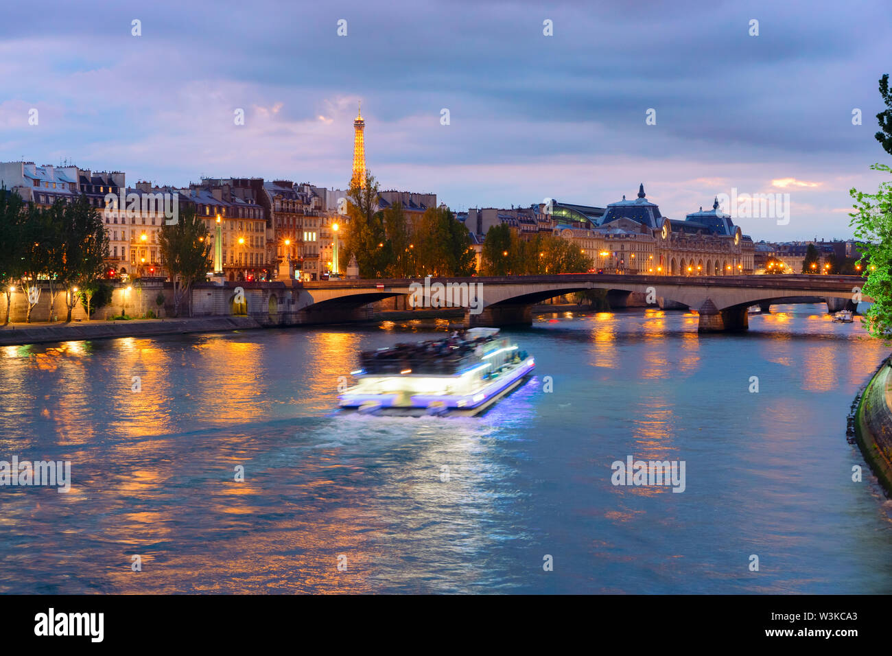 Pont Neuf and Cite island over Seine river with floating boat at night, France - Stock Image
