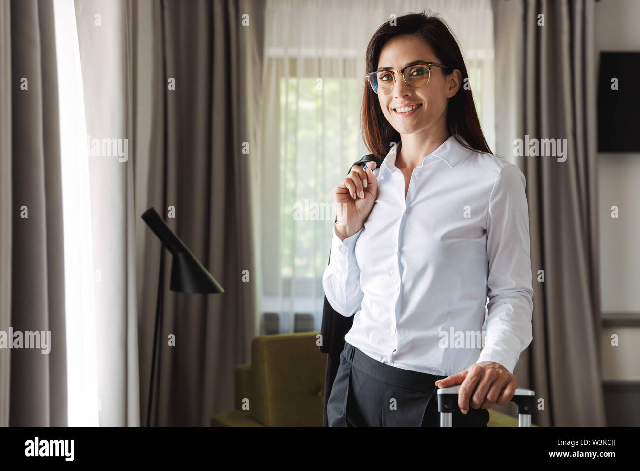 Image of a happy beautiful young business woman in formal wear clothes indoors at home with suitcase. - Stock Image