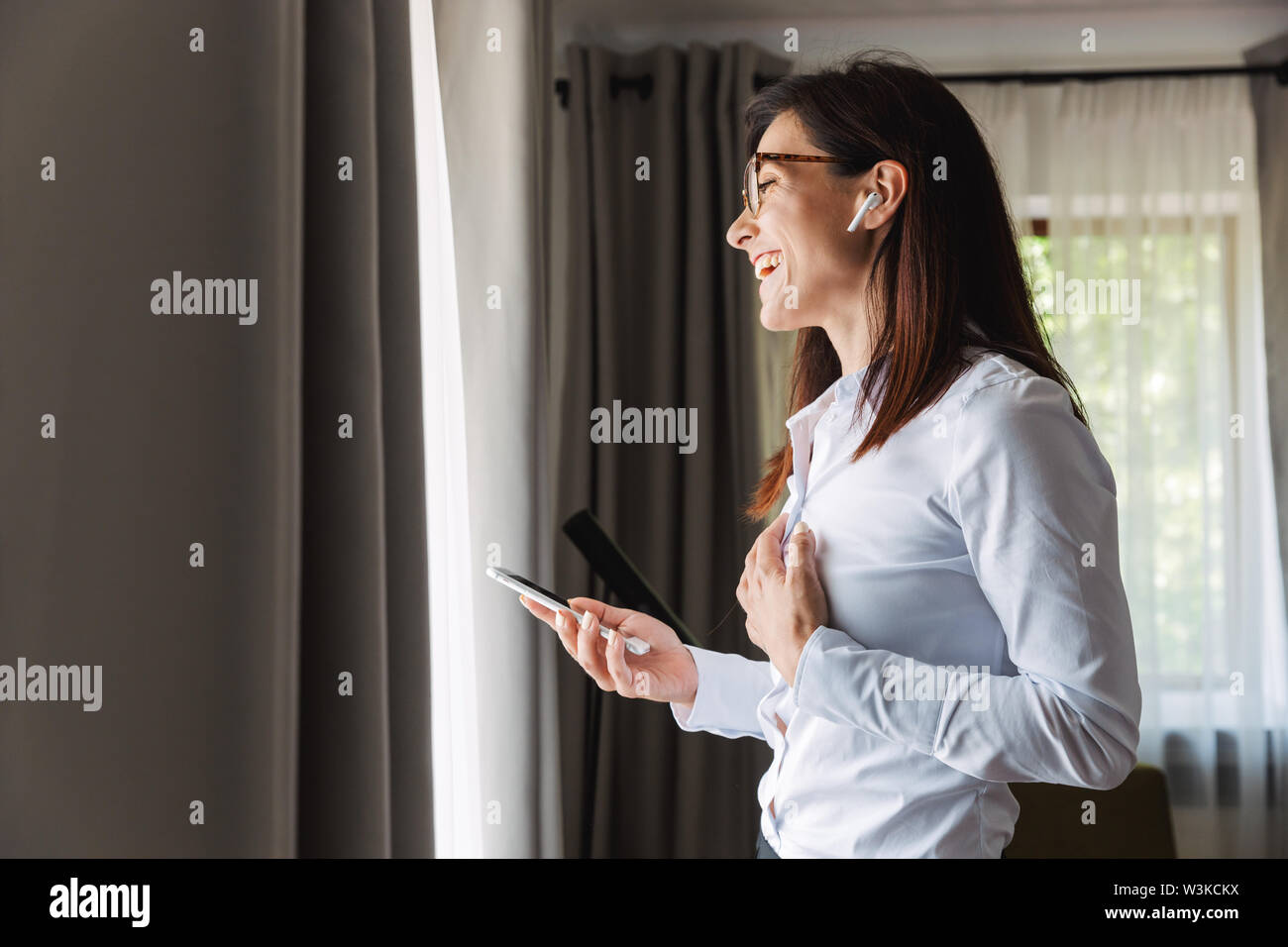 Image of an amazing happy beautiful young business woman in formal wear clothes indoors at home talking by mobile phone listening music with earphones - Stock Image