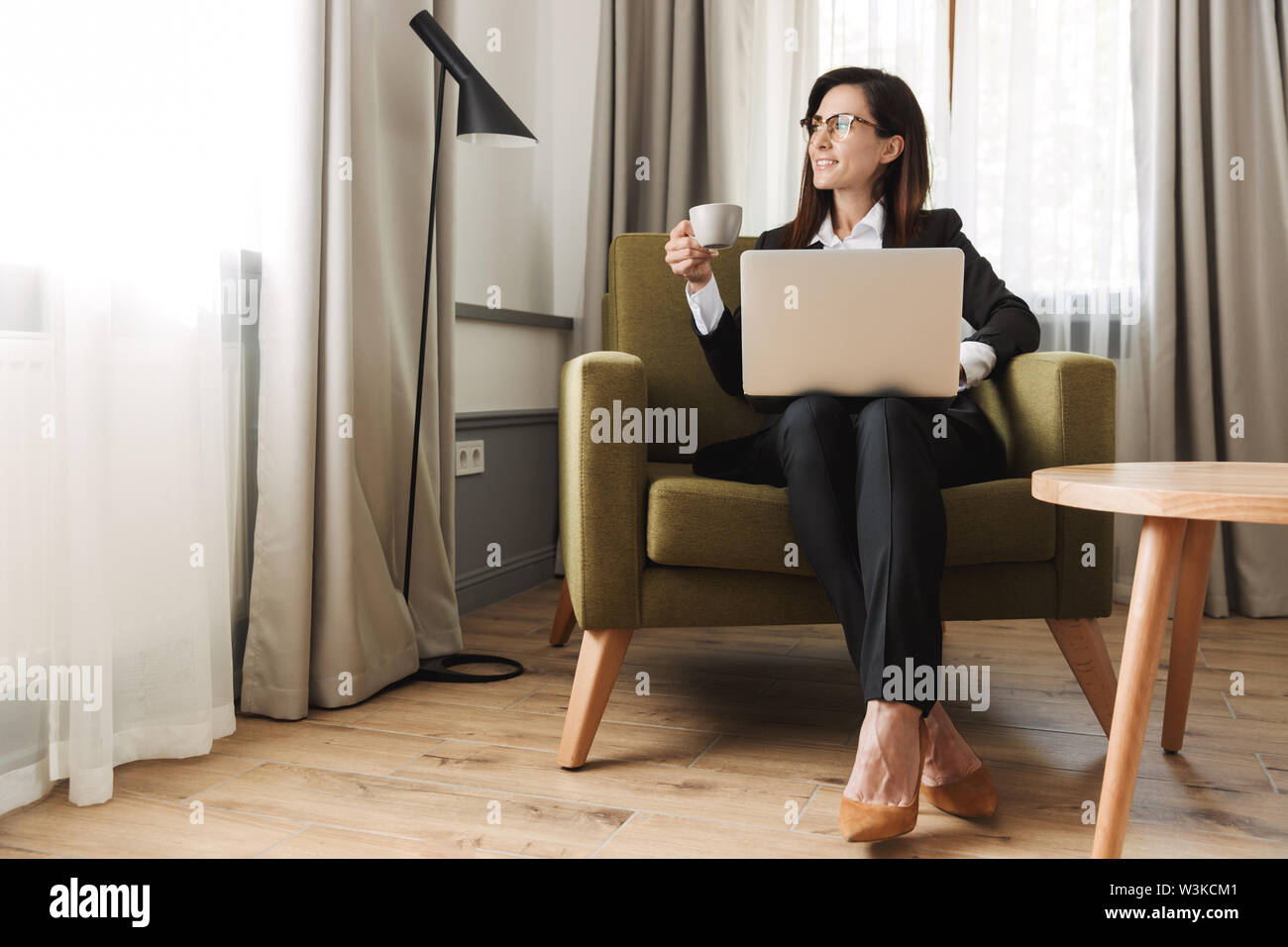 Photo of a beautiful young business woman in formal wear clothes indoors at home work with laptop computer drinking coffee. - Stock Image