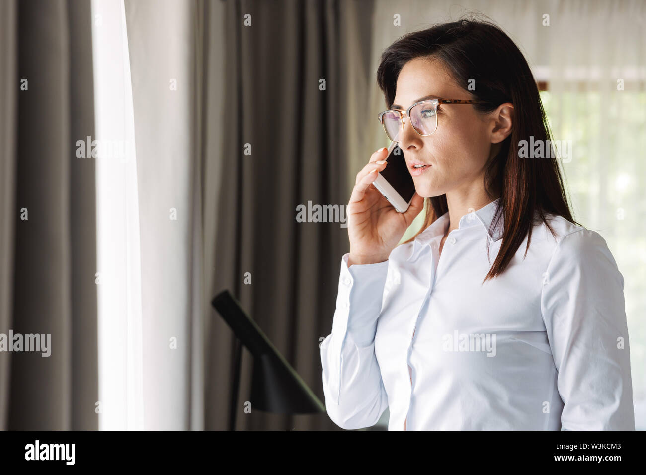 Image of an amazing beautiful young business woman in formal wear clothes indoors at home talking by mobile phone. - Stock Image