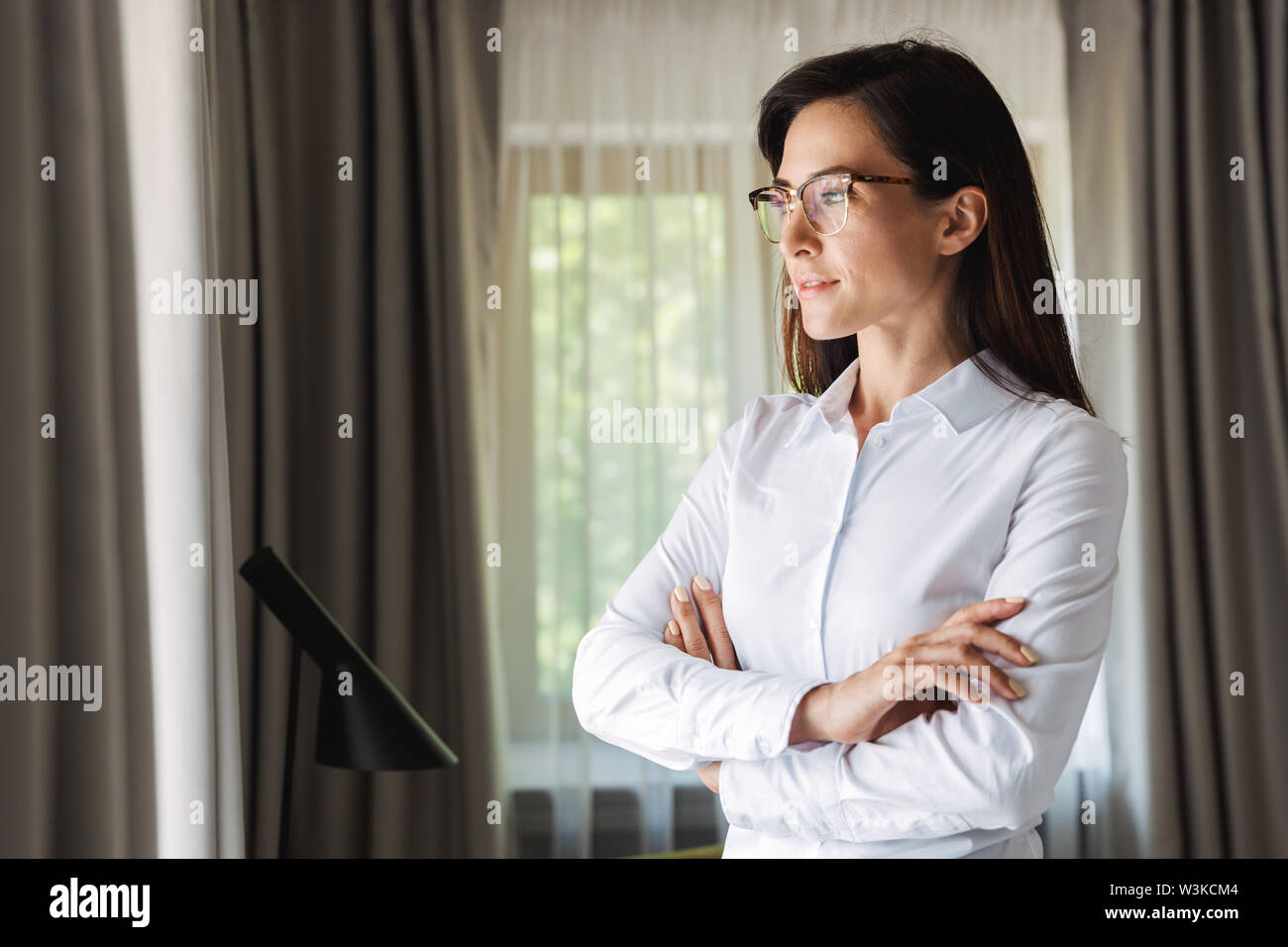 Image of an amazing beautiful young business woman in formal wear clothes indoors at home posing. - Stock Image