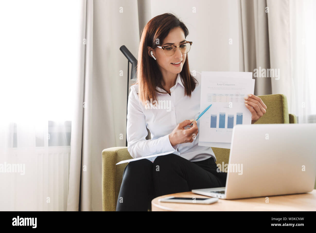 Image of an amazing concentrated beautiful young business woman in formal wear clothes indoors at home talking using laptop computer with earphones sh - Stock Image