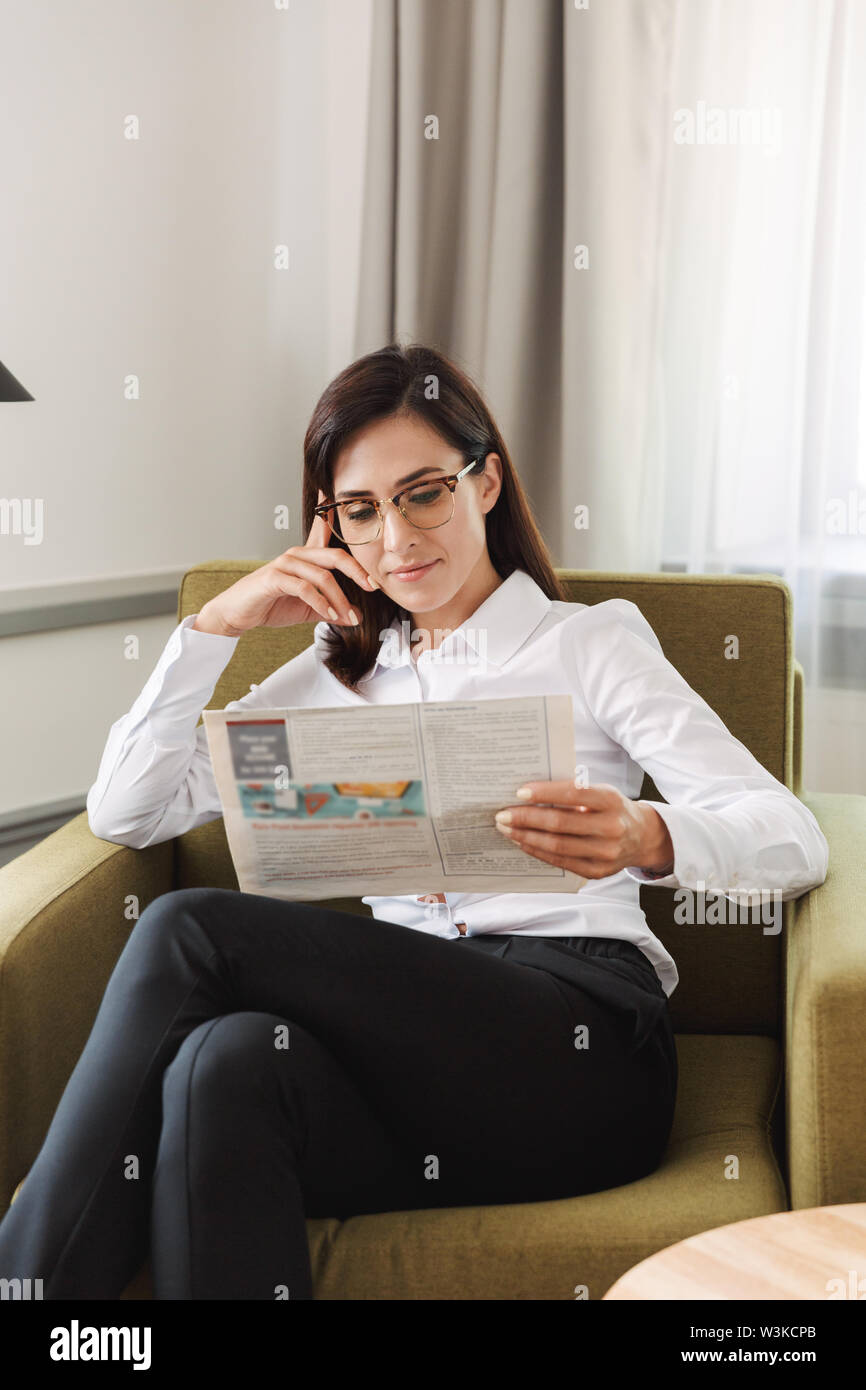 Image of an amazing concentrated beautiful young business woman in formal wear clothes indoors at home reading newspaper. - Stock Image