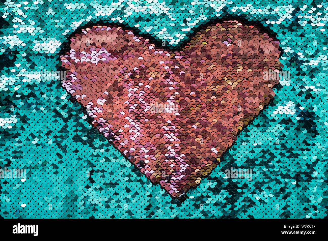 Coral heart made of sequins on turquoise background. Shiny fabric texture. - Stock Image