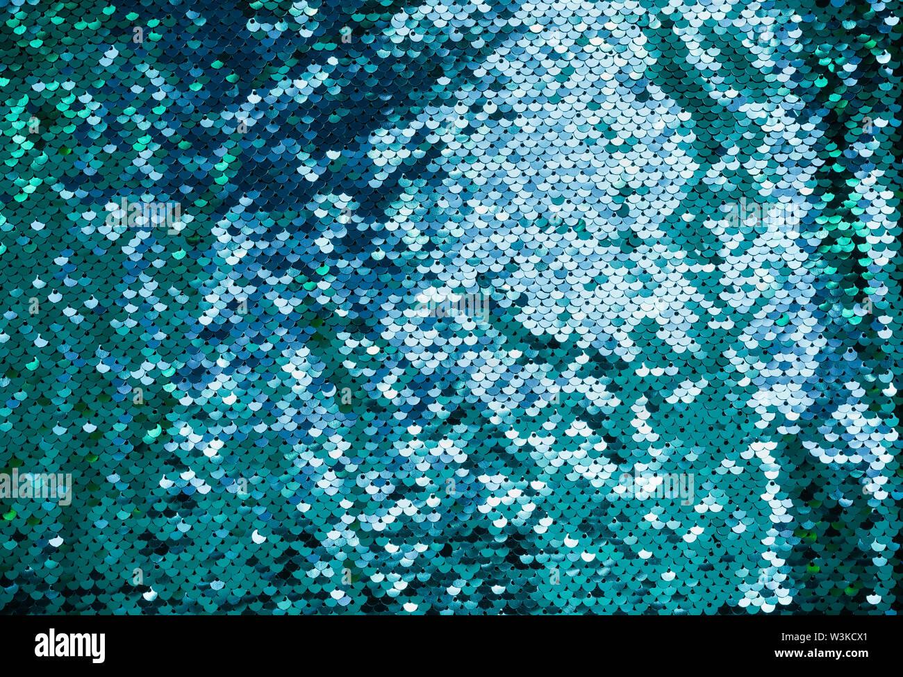 Shiny background made of turquoise sequins. Luxury scaly Background. - Stock Image