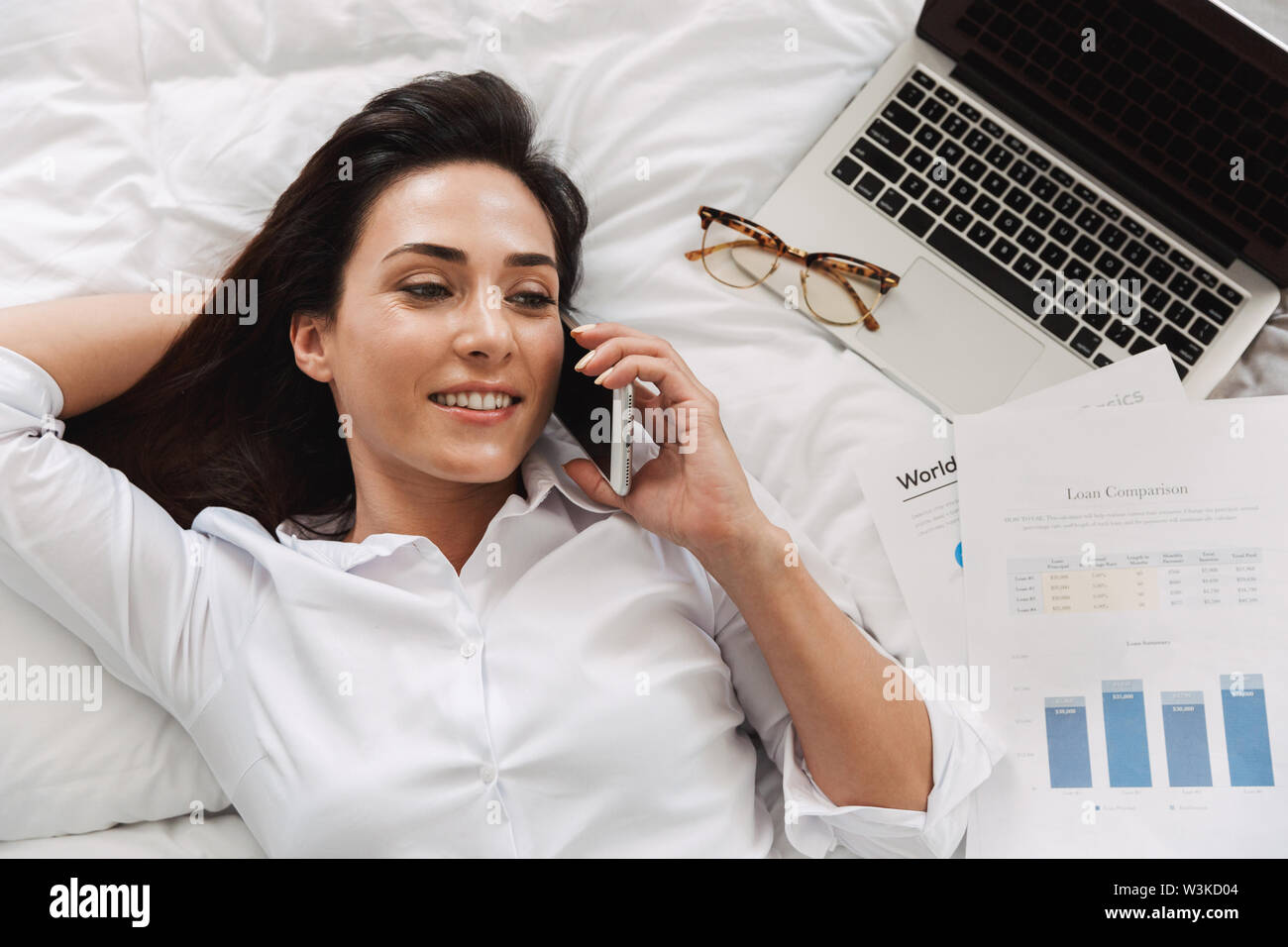 Image of an amazing beautiful happy young business woman in formal wear clothes indoors at home lies on bed talking by phone. - Stock Image