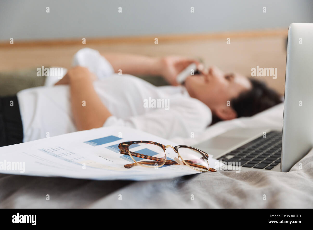 Image of an amazing beautiful young business woman in formal wear clothes indoors at home lies on bed talking by phone. Focus on glasses near woman. - Stock Image