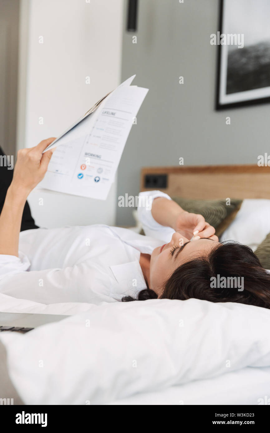 Image of an amazing beautiful young business woman in formal wear clothes indoors at home lies on bed talking by phone holding paper documents. - Stock Image