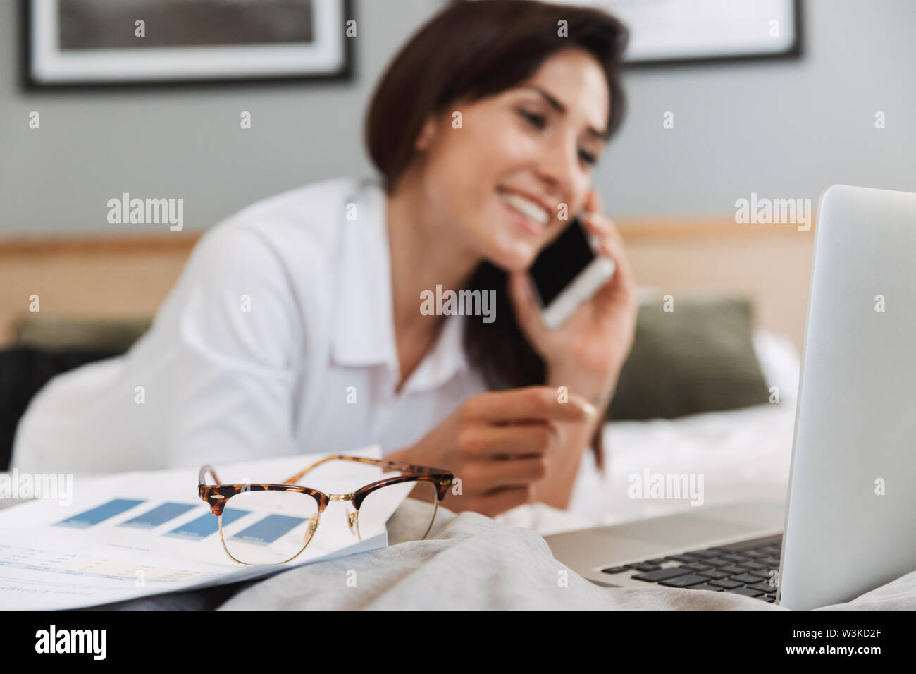 Image of an amazing happy beautiful young business woman in formal wear clothes indoors at home using laptop computer talking by phone. - Stock Image