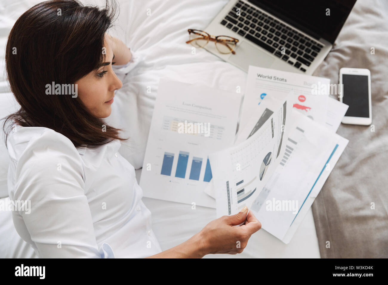 Image of an amazing beautiful young business woman in formal wear clothes indoors at home lies on bed looking at paper documents. - Stock Image