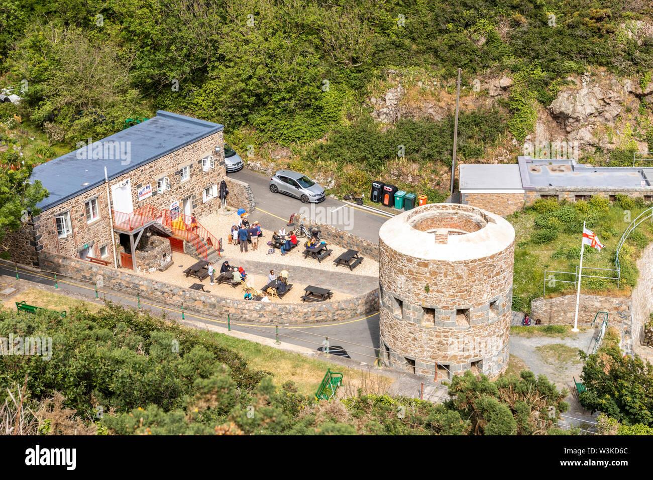 Looking down from the coastal path onto the tearooms and the Napoleonic loophole tower overlooking Petit Bot Bay, Guernsey, Channel Islands UK - Stock Image