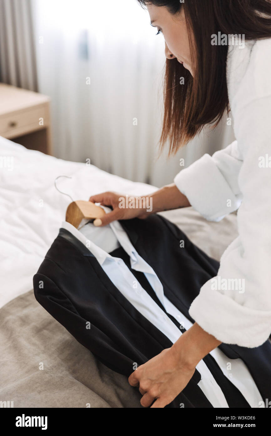 Cropped photo of an amazing young business woman holding formal wear clothes indoors at home. - Stock Image