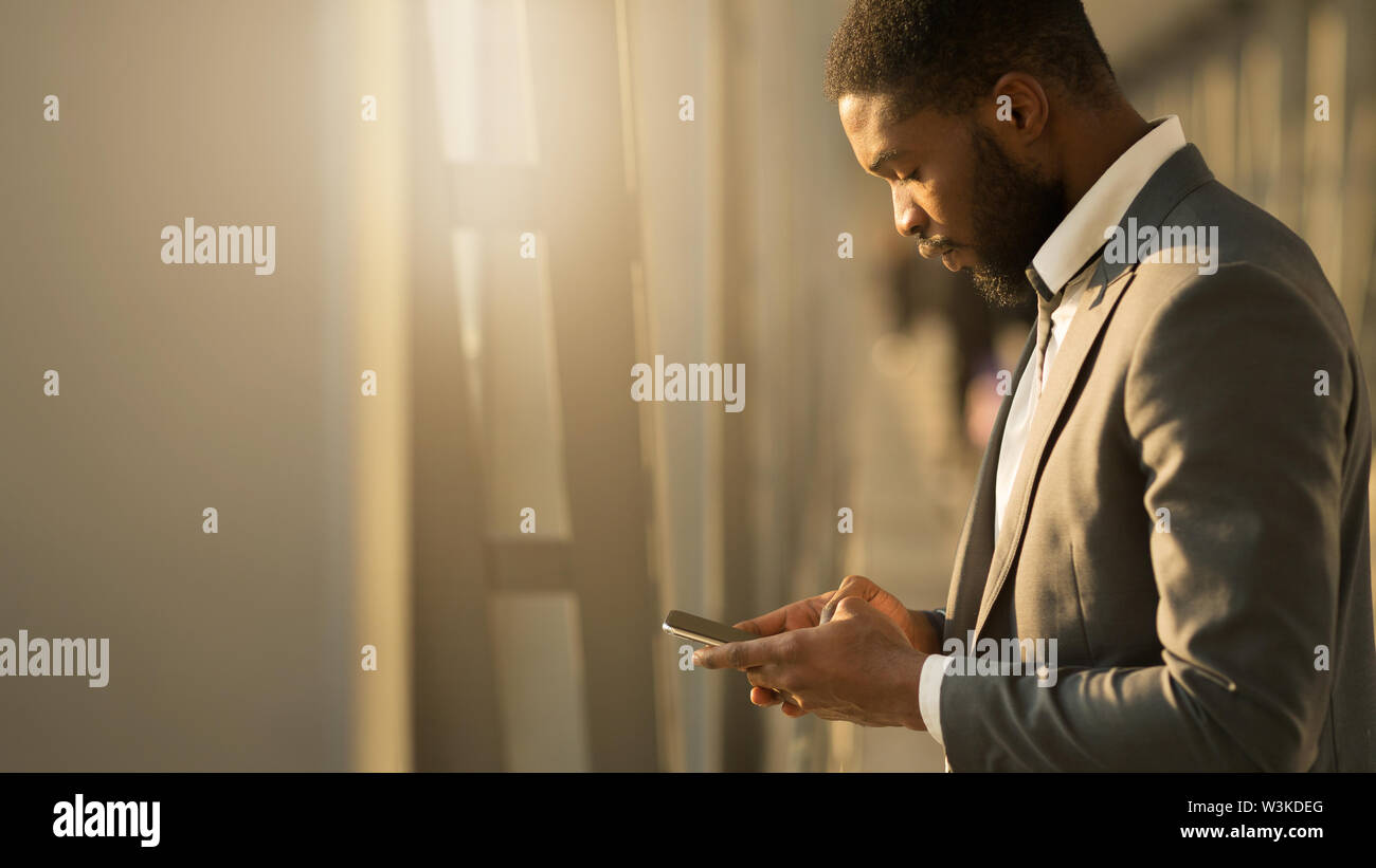 Afro Businessman Texting on Phone, Waiting for Departure - Stock Image