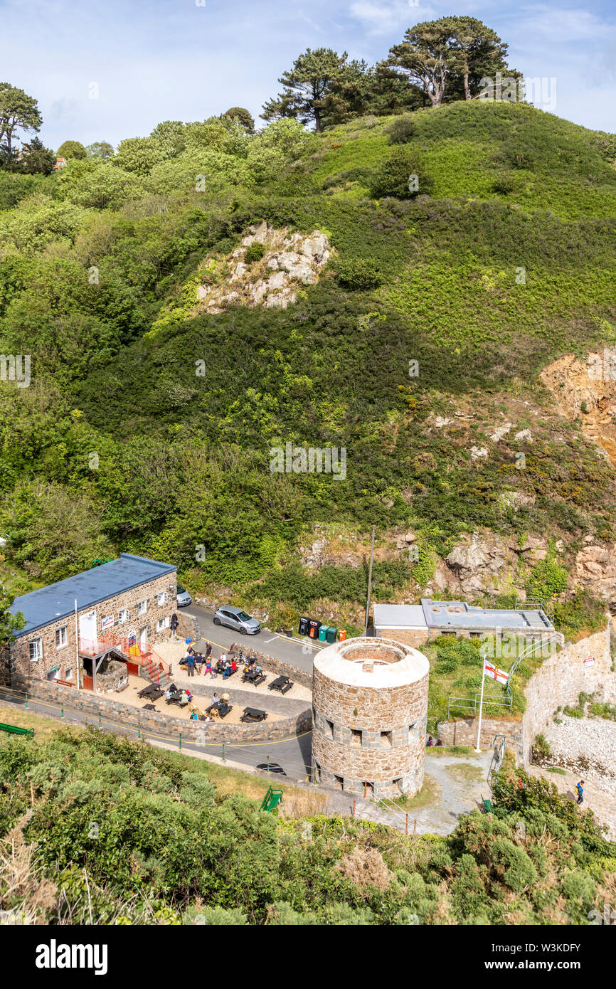 Looking down from the coastal path onto the Napoleonic loophole tower overlooking Petit Bot Bay on the beautiful rugged south coast of Guernsey UK - Stock Image