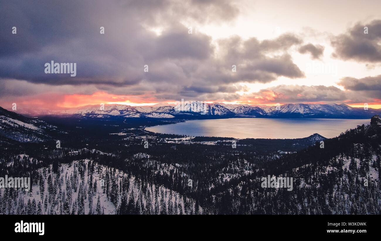 An Ariel shot of snowy forest near South Lake Tahoe with cloudy sky - Stock Image
