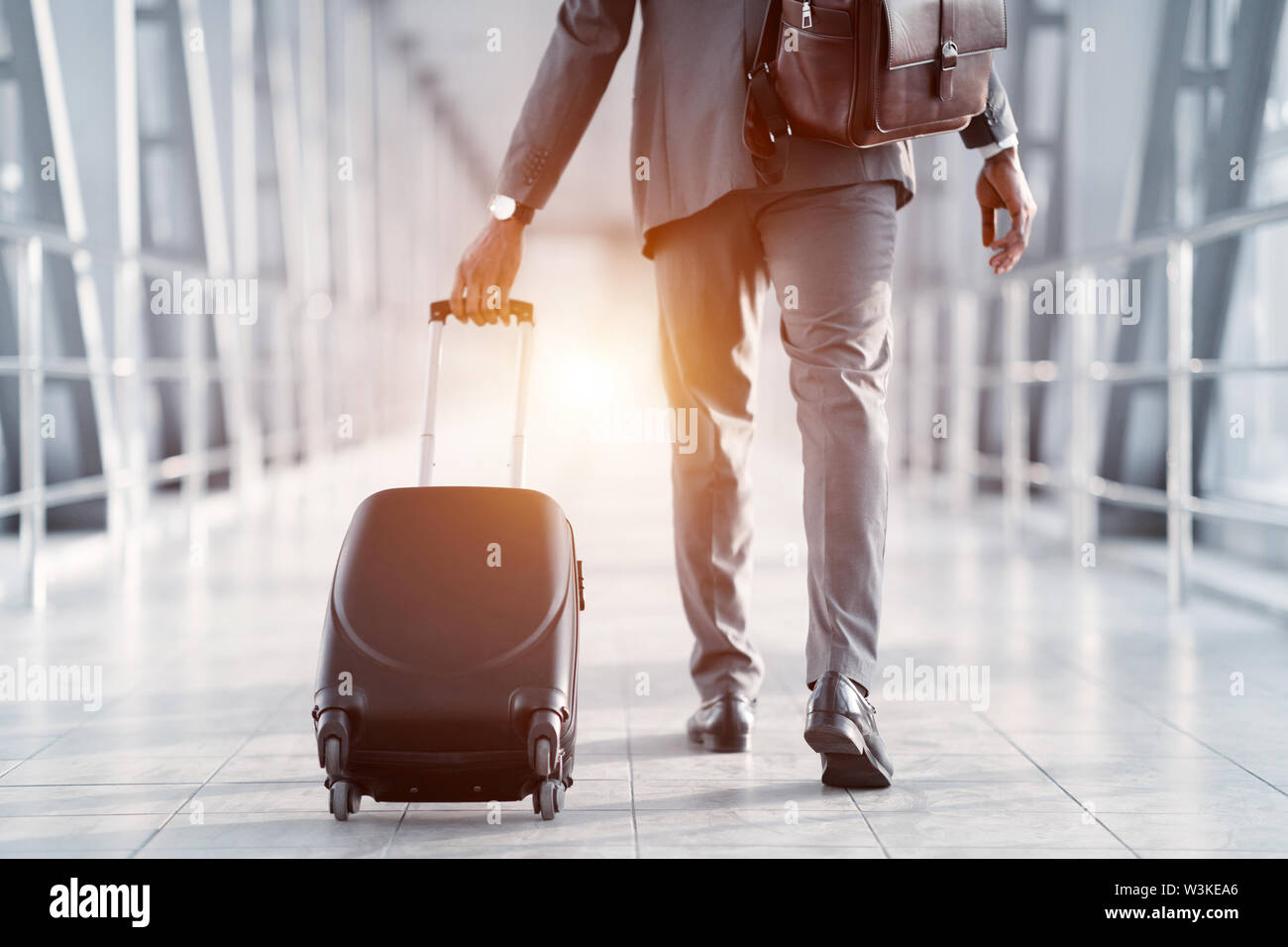 Businessman Hurrying on Plane, Walking Through Passenger Bridge - Stock Image