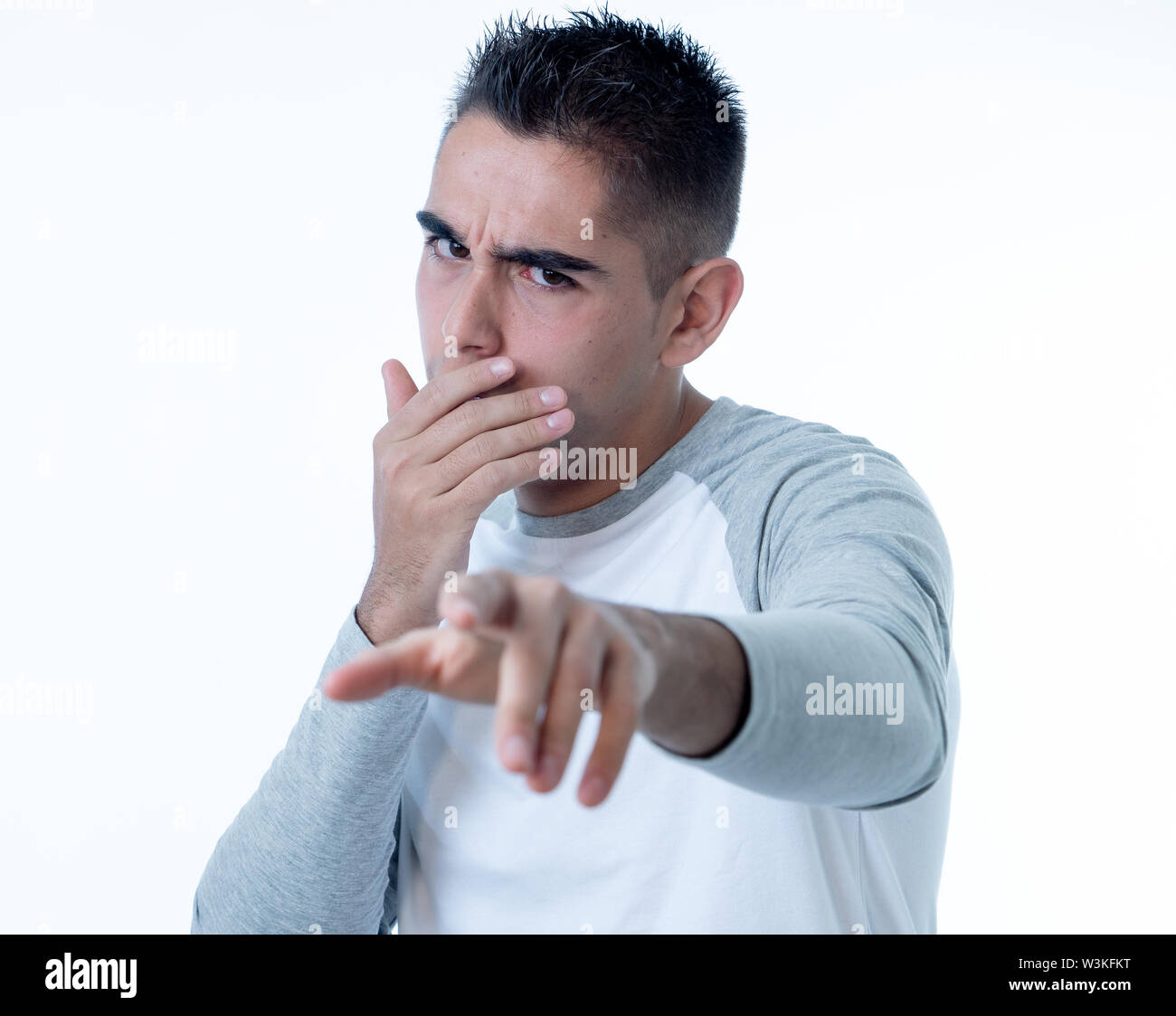 Portrait of young man in shock with scared face making frightened gestures and pointing at something scaring. Human emotions feelings and facial expre - Stock Image