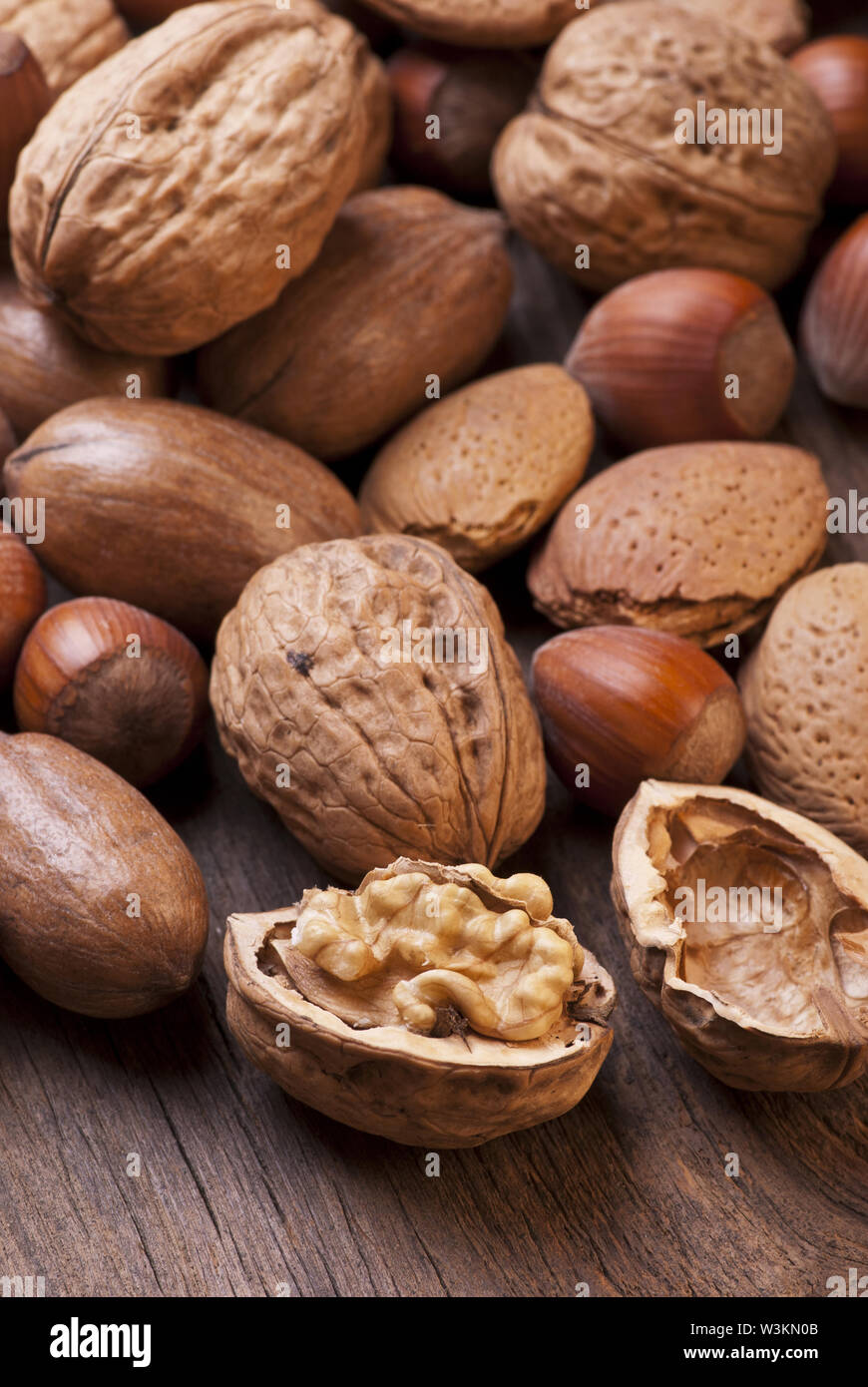 closeup of different types of dried fruit including pecans, almonds and hazelnuts in shell on rustic wooden table Stock Photo