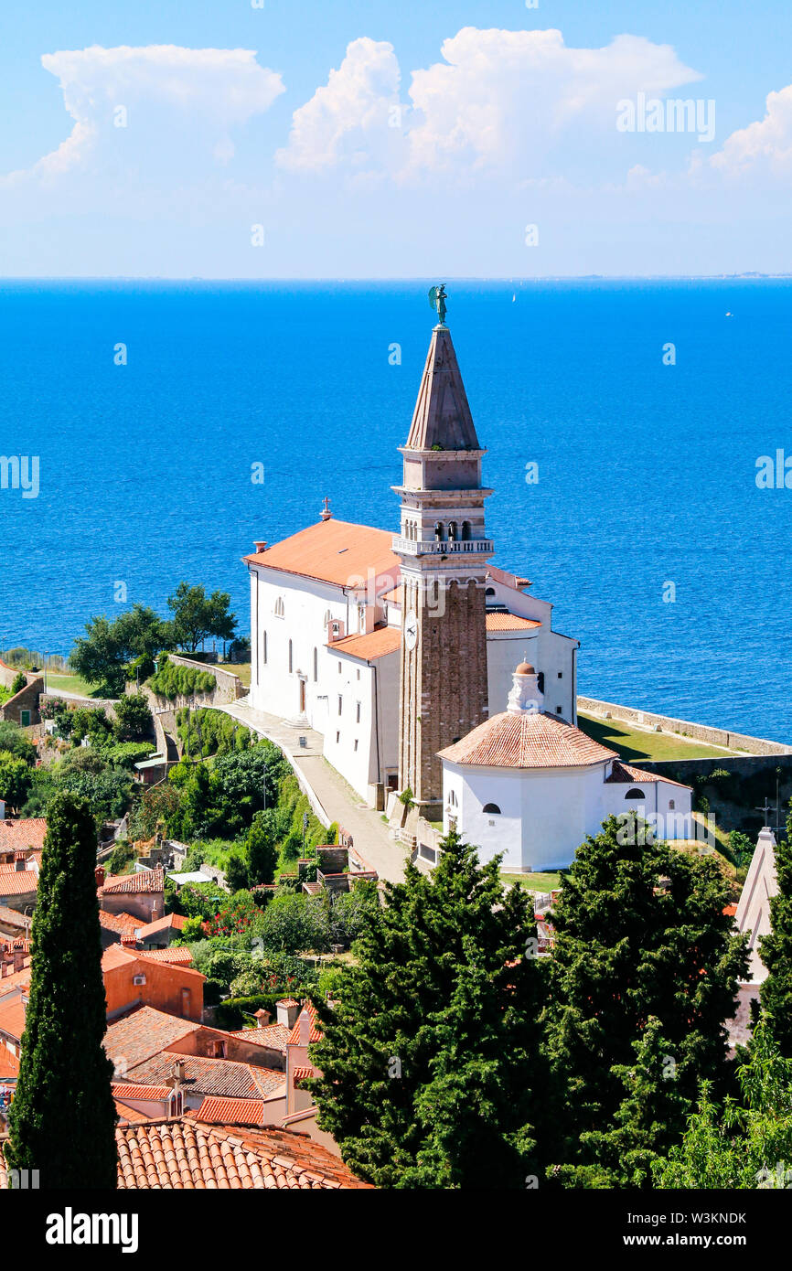 View of St George's Church and the red tiled rooftops of the old town of Piran in Slovenia, with the Adriatic Sea in the background Stock Photo