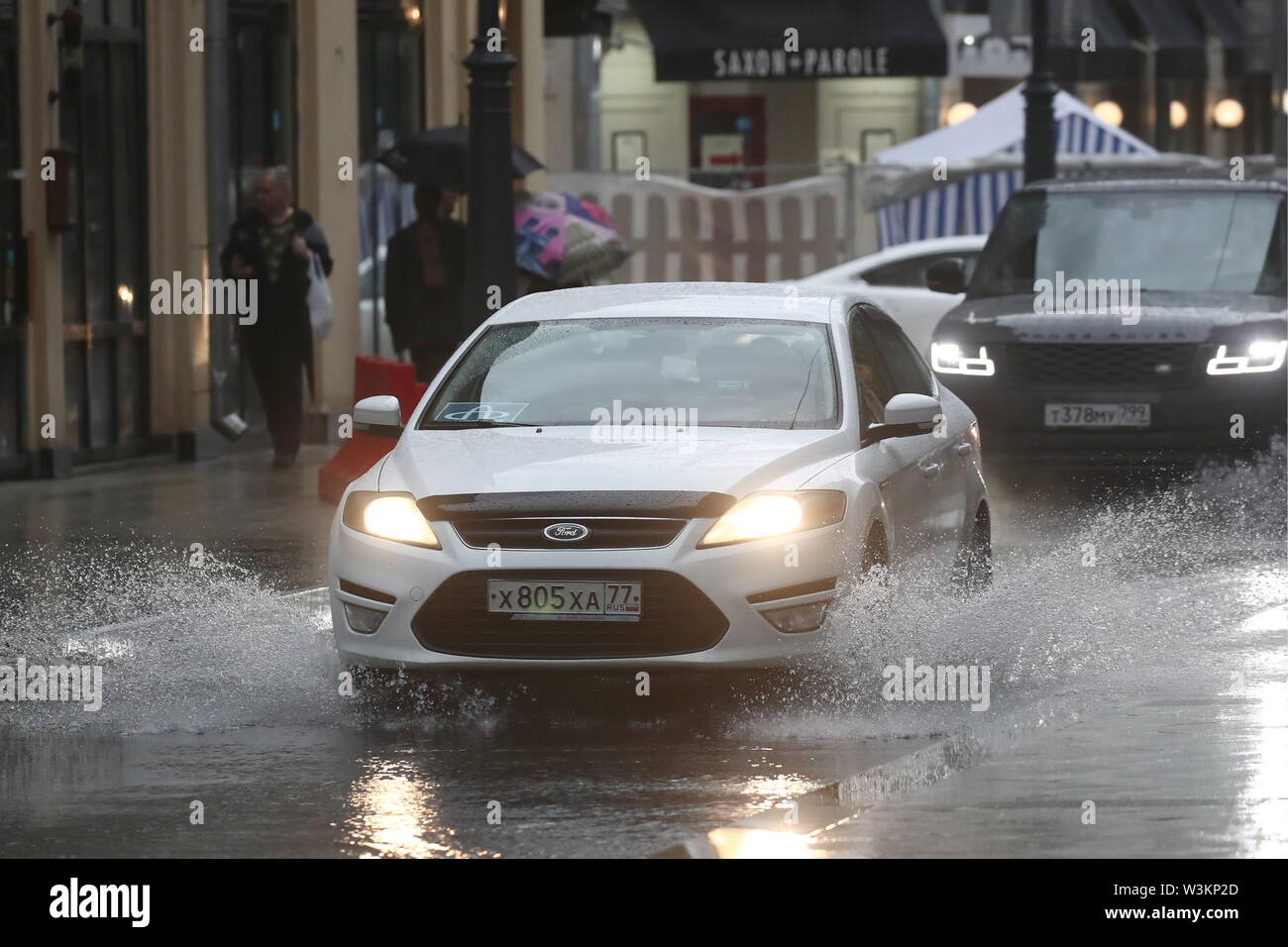 MOSCOW, RUSSIA - JULY 16, 2019: A car drives through water in Bolshoi Palashevsky Lane. Valery Sharifulin/TASS - Stock Image
