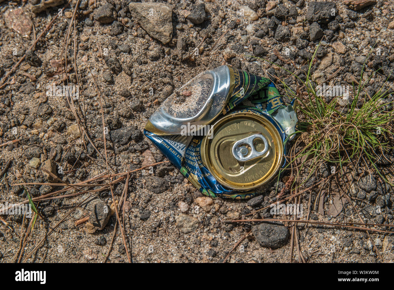 A crushed soda or beer can laying on the ground near the beach at the Lake on a sunny day in summer - Stock Image