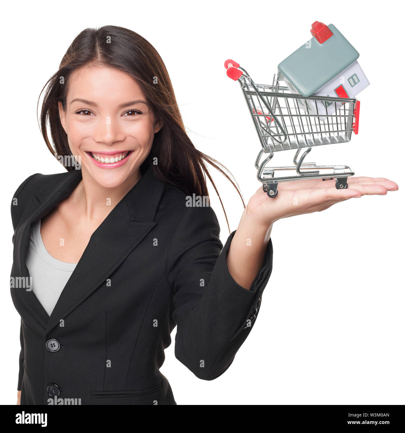 Real estate agent selling home holding mini house in shopping cart. Female realtor in business suit showing model house smiling happy isolated on white background. Multiracial Asian woman agent. Stock Photo
