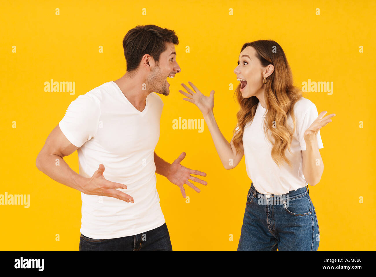 Portrait of happy couple man and woman in basic t-shirts rejoicing with gestures while looking at each other isolated over yellow background - Stock Image