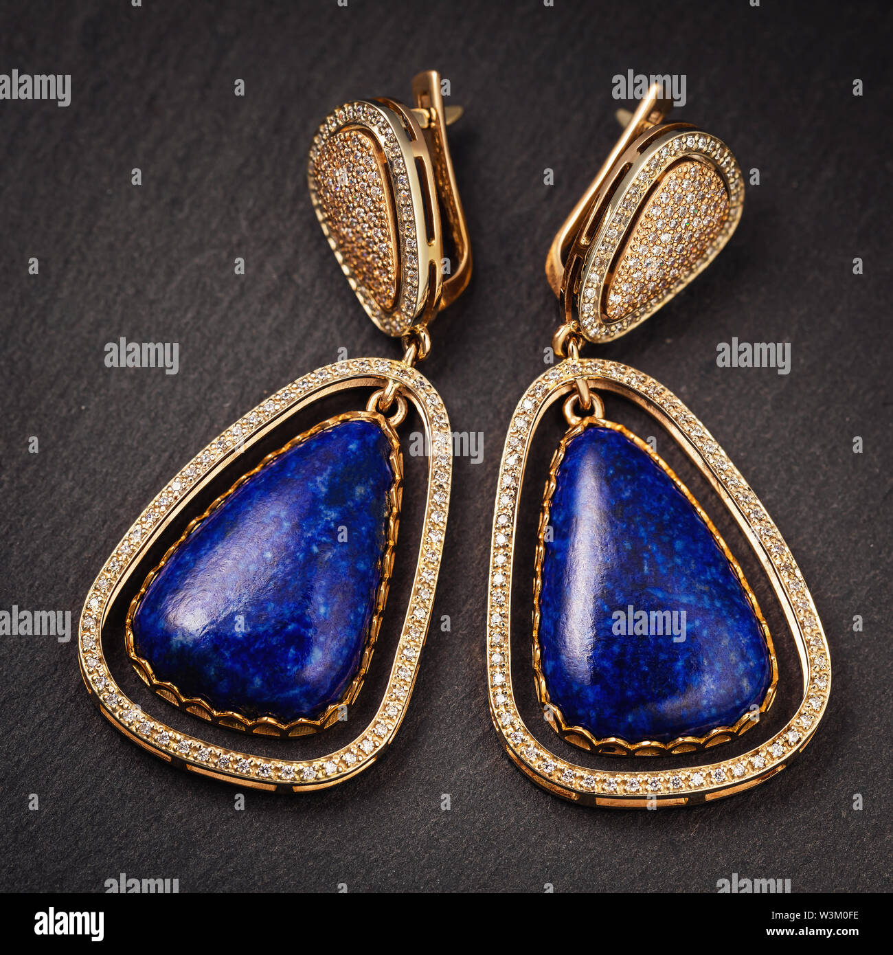 Beautiful gold earrings with lapis lazuli and small cubic zirconias, close-up Stock Photo