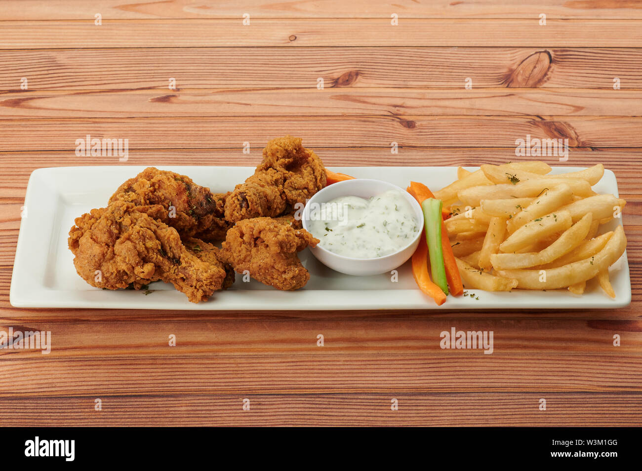 Fried chicken with tartar sauce in plate on wooden table - Stock Image
