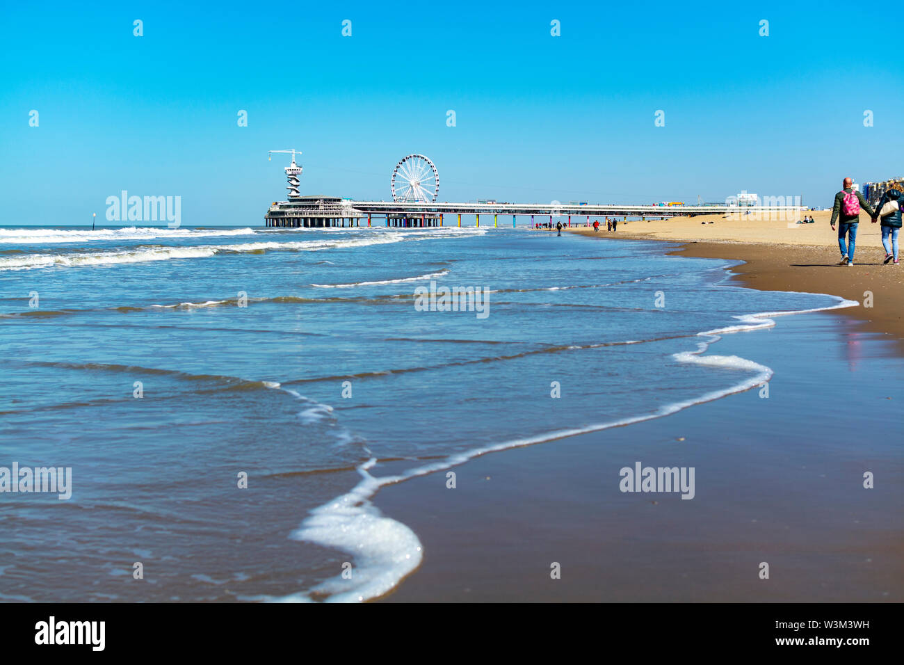 People walking in sunny day on North sea beach in Netherlands near Scheveningen, tourist and vacation destination in Europe - Stock Image