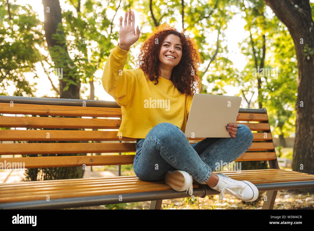 Image of a smiling cheerful young beautiful curly student girl sitting outdoors in nature park using laptop computer waving to friends. - Stock Image