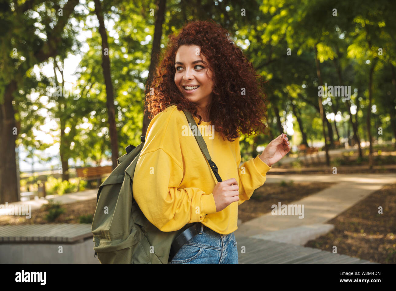 Photo of a smiling young beautiful curly student girl outdoors in nature park walking with backpack. - Stock Image