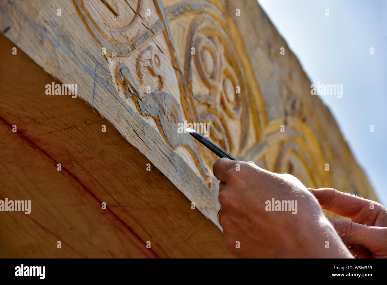 Carving motif into oak beam on traditional reconstruction of medieval timber framed hall - Stock Image