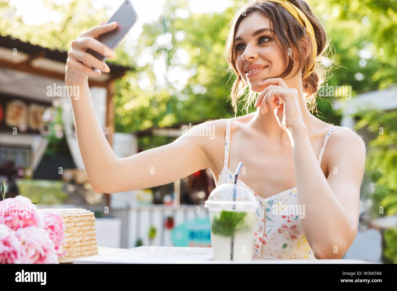 Image of a beautiful happy young amazing woman sitting at the table with flowers in green park take a selfie by mobile phone. - Stock Image